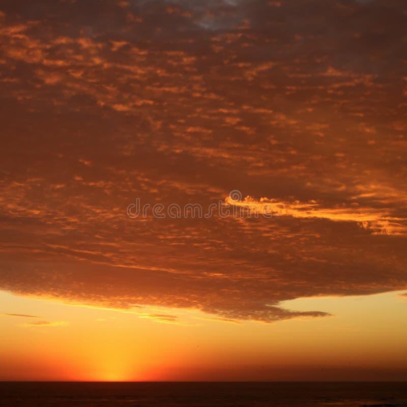Puesta del sol carmesí volcánica dramática sobre el Océano Pacífico foto de archivo libre de regalías