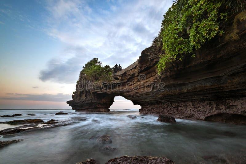 Puesta del sol cerca de la señal turística famosa de la isla de Bali - templo de la porción y de Batu Bolong de Tanah imagenes de archivo