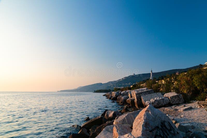Puesta del sol cerca del faro viejo de Trieste fotos de archivo