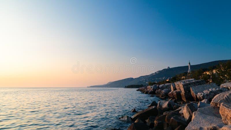 Puesta del sol cerca del faro viejo de Trieste foto de archivo