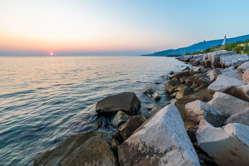 Puesta del sol cerca del faro viejo de Trieste imagen de archivo