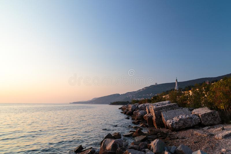 Puesta del sol cerca del faro viejo de Trieste fotografía de archivo