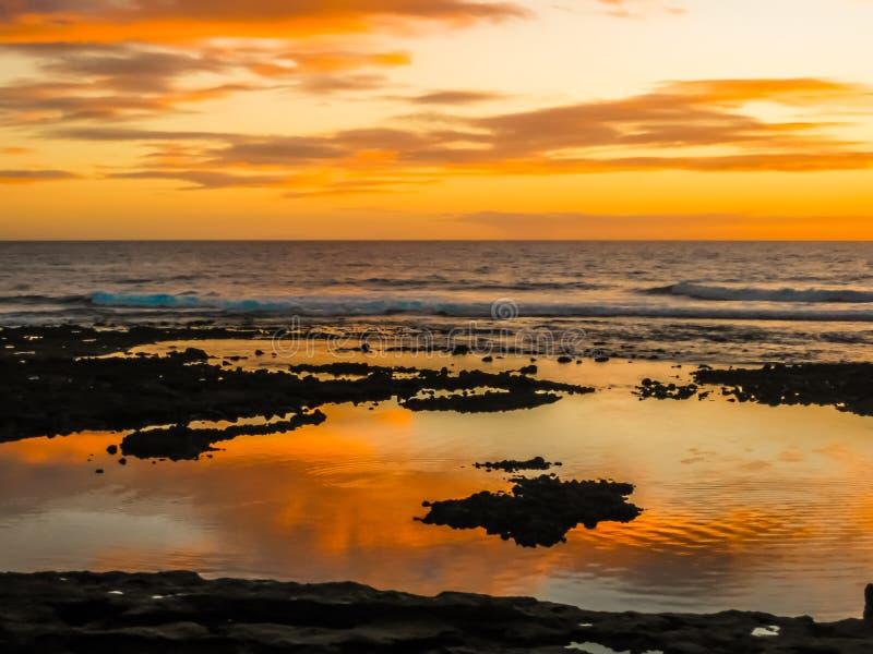 Puesta del sol colorida con las nubes que reflejan en el océano imágenes de archivo libres de regalías