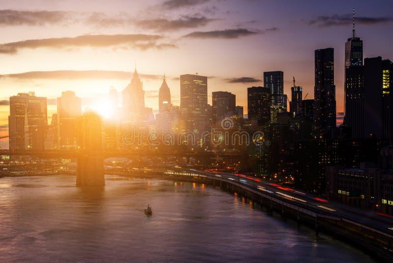 Puesta del sol colorida detrás del puente de Brooklyn y de los rascacielos del th imagen de archivo
