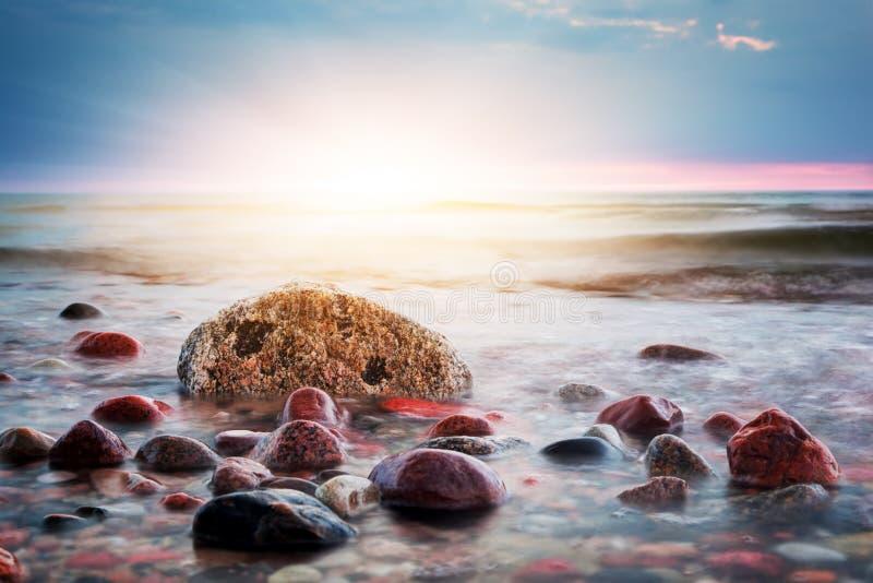 Puesta del sol colorida dramática en una playa rocosa Mar Báltico imagen de archivo