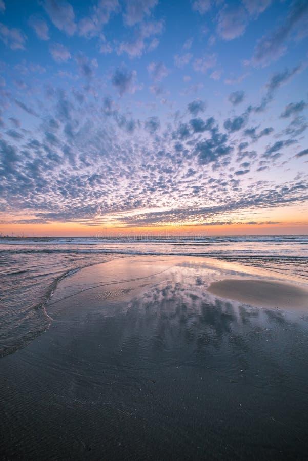 Puesta del sol colorida en la playa holandesa con las reflexiones hermosas de las nubes en arena mojada fotografía de archivo