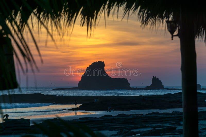 Puesta del sol colorida en la playa en Nicaragua con una roca en el frente foto de archivo libre de regalías