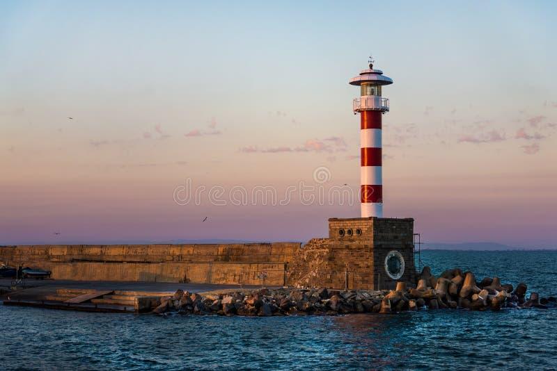 Puesta del sol colorida sobre el faro de la orilla de mar de Bourgas fotos de archivo
