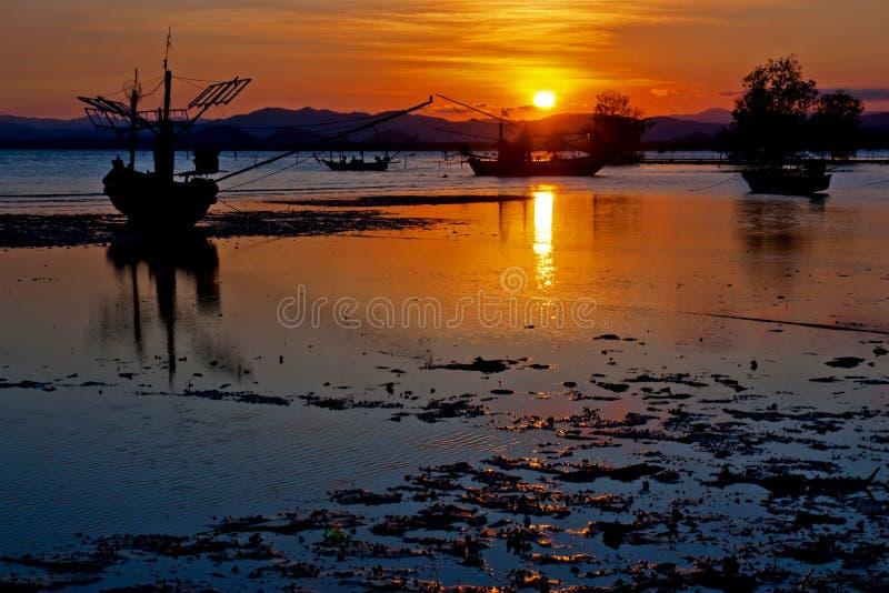 Puesta del sol con el barco de pesca en la playa imagen de archivo