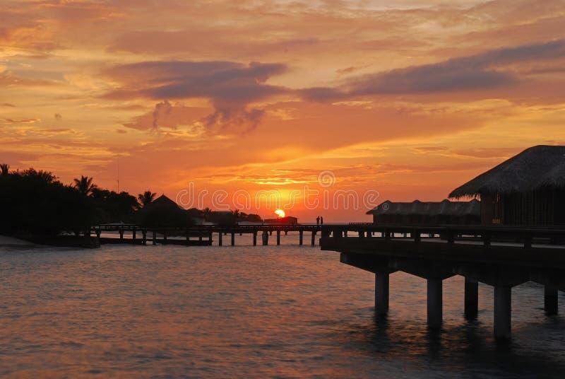 Puesta del sol con el cielo natural hermoso contra el chalet del overwater foto de archivo