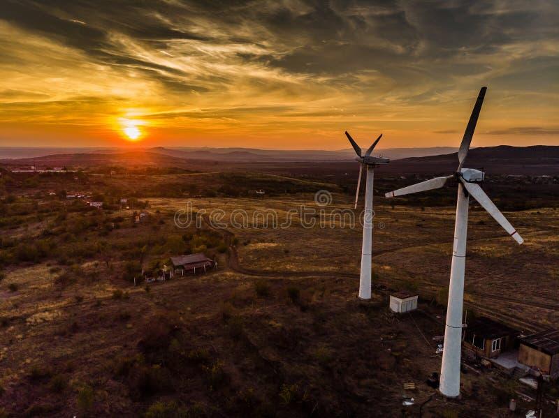 Puesta del sol con el generador de poder de las turbinas de viento fotografía de archivo libre de regalías