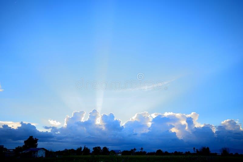 Puesta del sol con el haz del sol detrás de las nubes oscuras imagenes de archivo