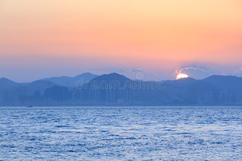 Puesta del sol con el mar y las montañas fotografía de archivo libre de regalías