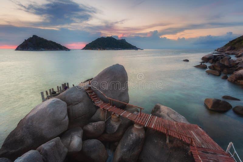 Puesta del sol con el paseo marítimo sobre rocas en Koh Tao imagenes de archivo