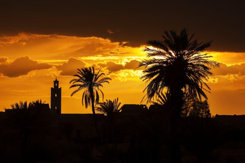 Puesta del sol con la mezquita y las siluetas de la palma datilera. imagen de archivo