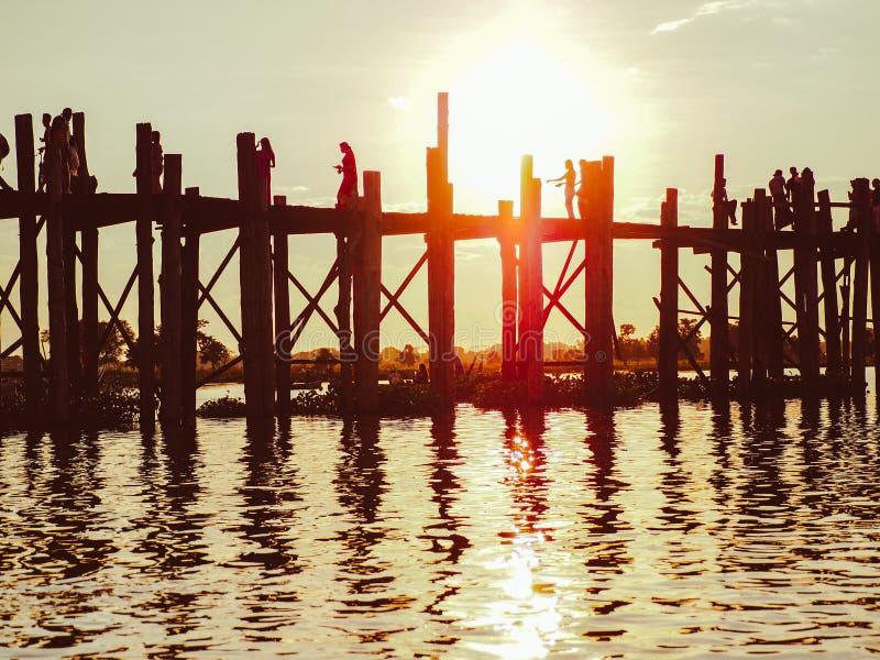 Puesta del sol con la silueta de la gente que camina en el puente U-Bein foto de archivo libre de regalías