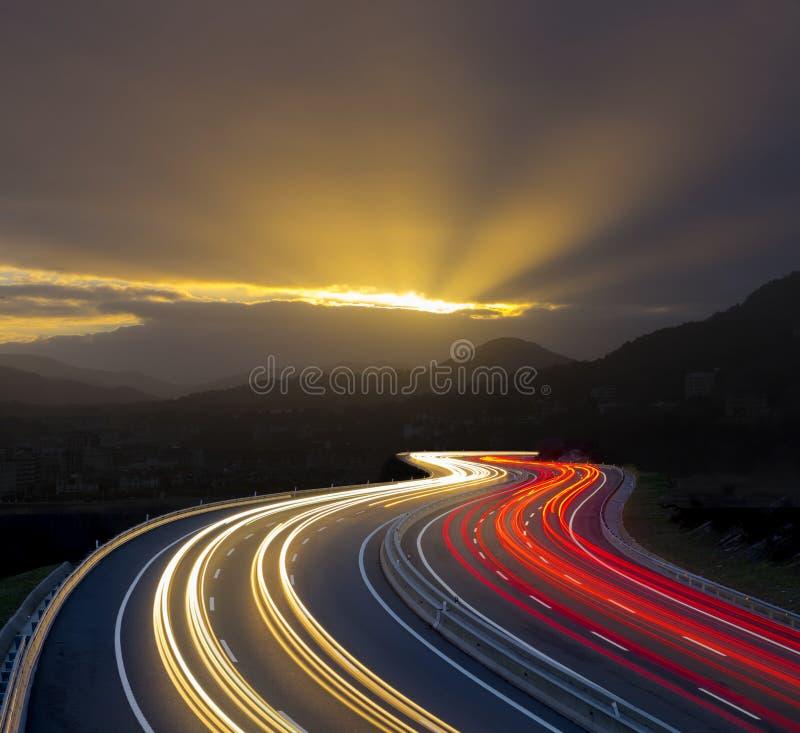 Puesta del sol con las luces del coche en la carretera fotografía de archivo libre de regalías