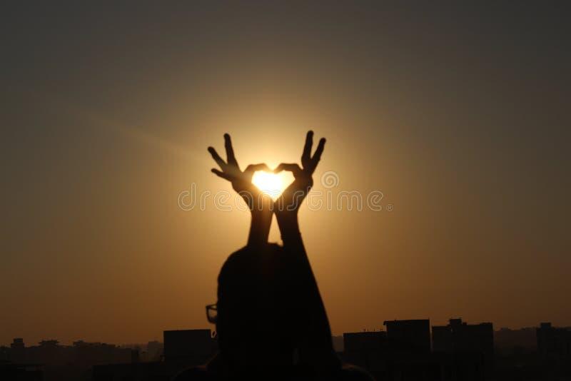 Puesta del sol con las manos de la forma del corazón imágenes de archivo libres de regalías