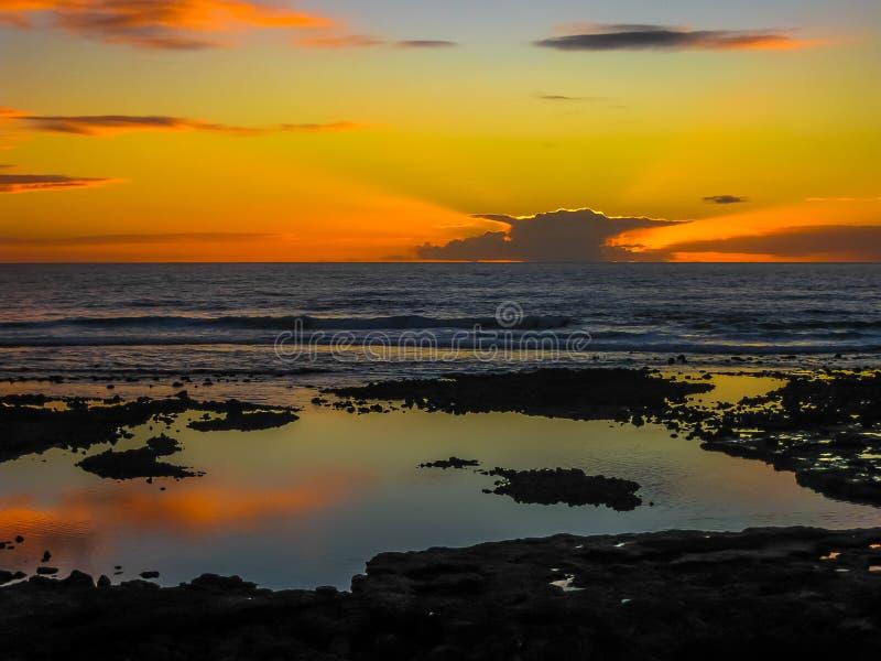 Puesta del sol con las nubes que reflejan en el océano fotos de archivo