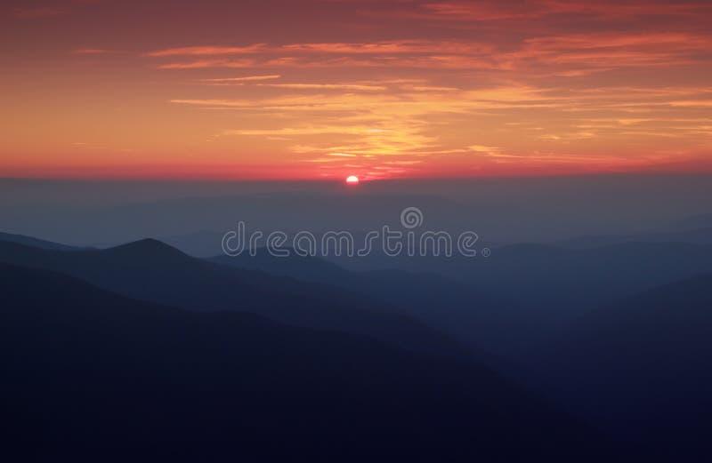 Puesta del sol con las siluetas de la montaña en sombra de la niebla fotografía de archivo libre de regalías