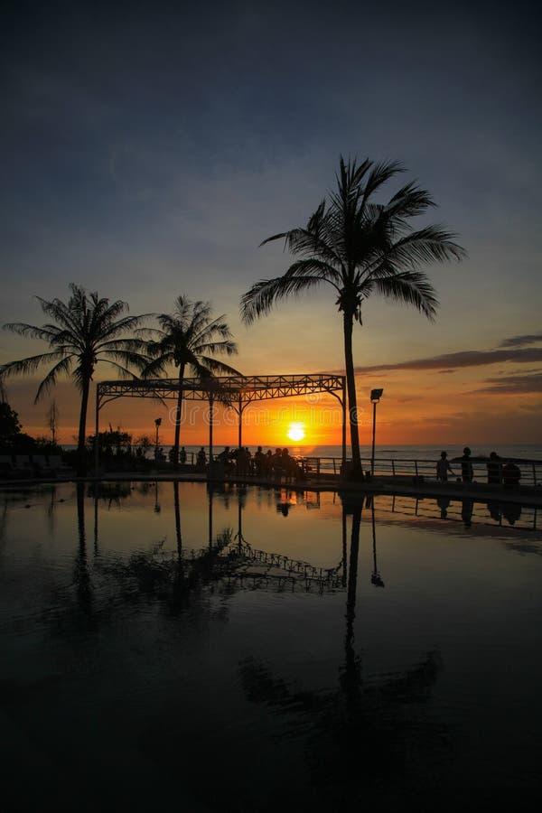 Puesta del sol con los árboles por el fondo del mar en Bali imagen de archivo