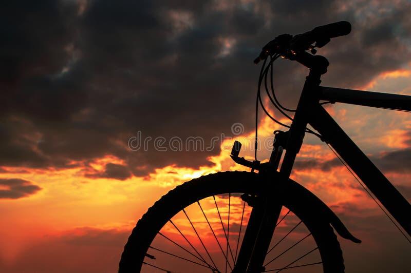 Puesta del sol con una bicicleta imagenes de archivo