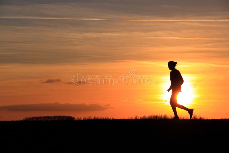 Puesta del sol corriente de la silueta de la mujer fotos de archivo libres de regalías