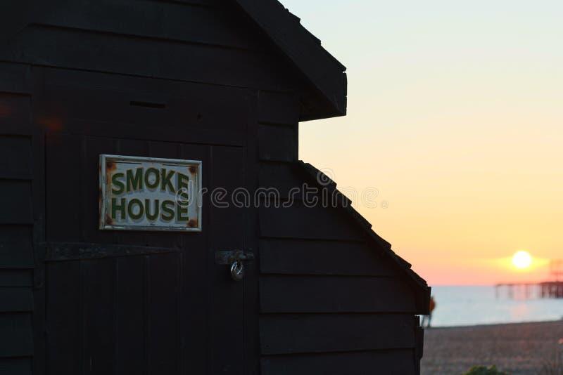 Puesta del sol de la choza de la playa de Brighton con el embarcadero viejo foto de archivo