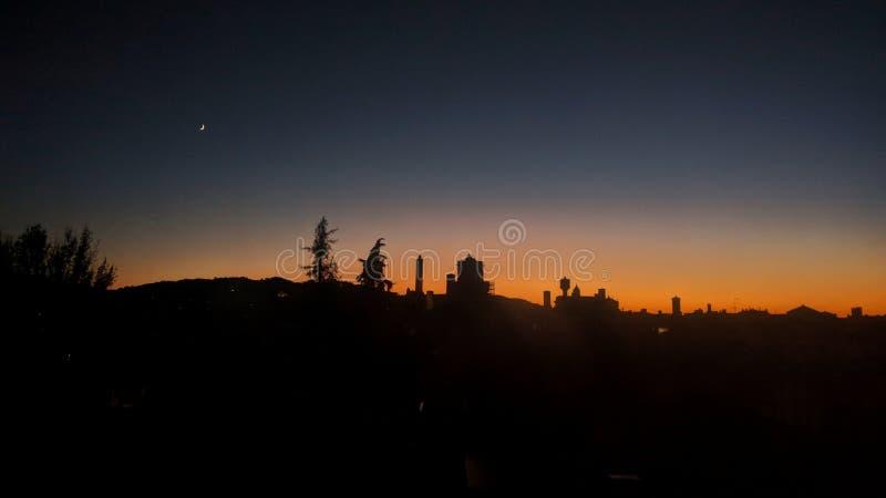 Puesta del sol de la ciudad con las torres, los árboles y la luna imágenes de archivo libres de regalías