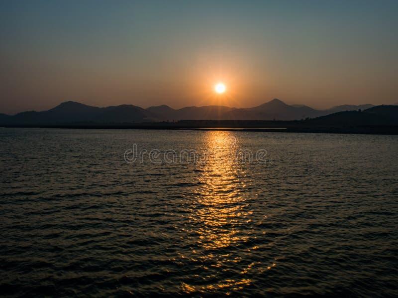 Puesta del sol de la colina sobre el agua foto de archivo