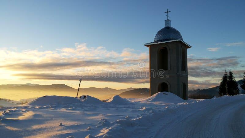 Puesta del sol de la iglesia de la montaña del invierno fotos de archivo libres de regalías