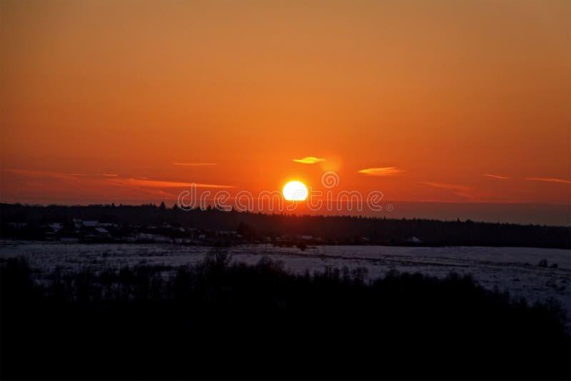 Puesta del sol de la nieve del invierno sobre el pueblo en el bosque fotografía de archivo