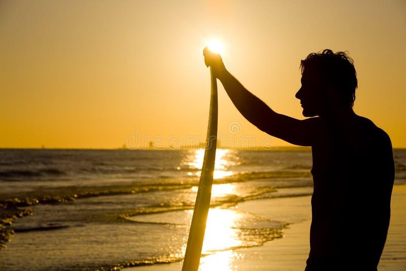 Puesta del sol de la persona que practica surf imagen de archivo libre de regalías