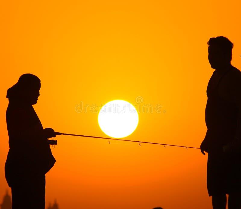 Puesta del sol de la pesca imagenes de archivo