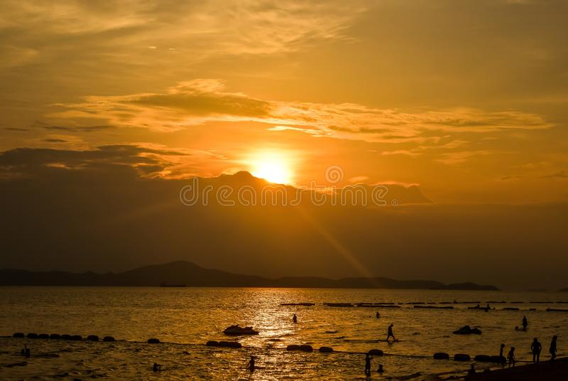 Puesta del sol de la playa con la gente de la silueta arenosa en el cielo de oro colorido de la hora del mar del verano tropical  fotos de archivo