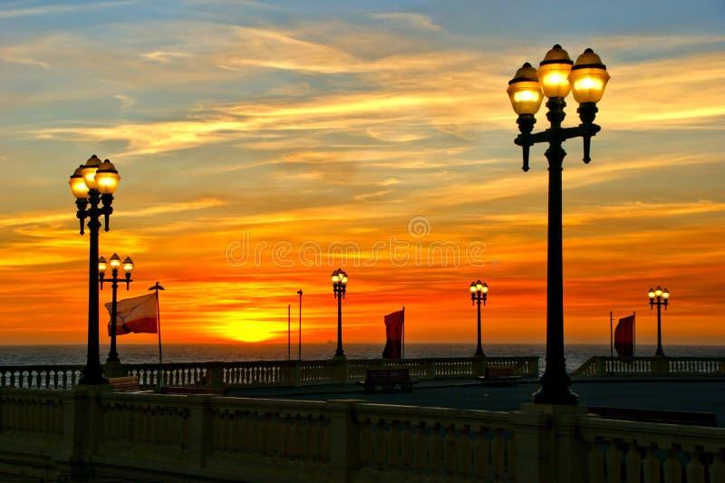 Puesta del sol de la playa con las lámparas en Oporto imagen de archivo libre de regalías