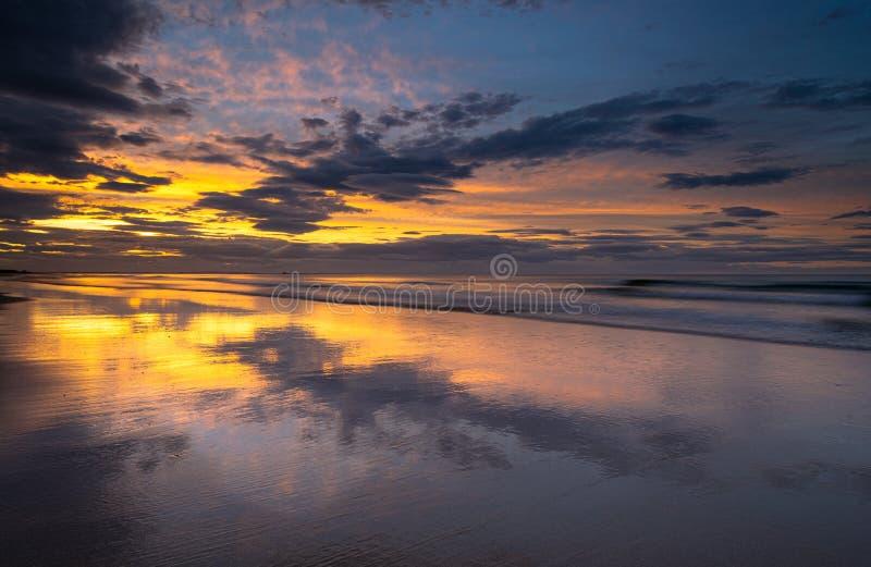 Puesta del sol de la playa de la costa costa en la orilla en Bamburgh, Northumberland en Inglaterra del este del norte fotos de archivo libres de regalías