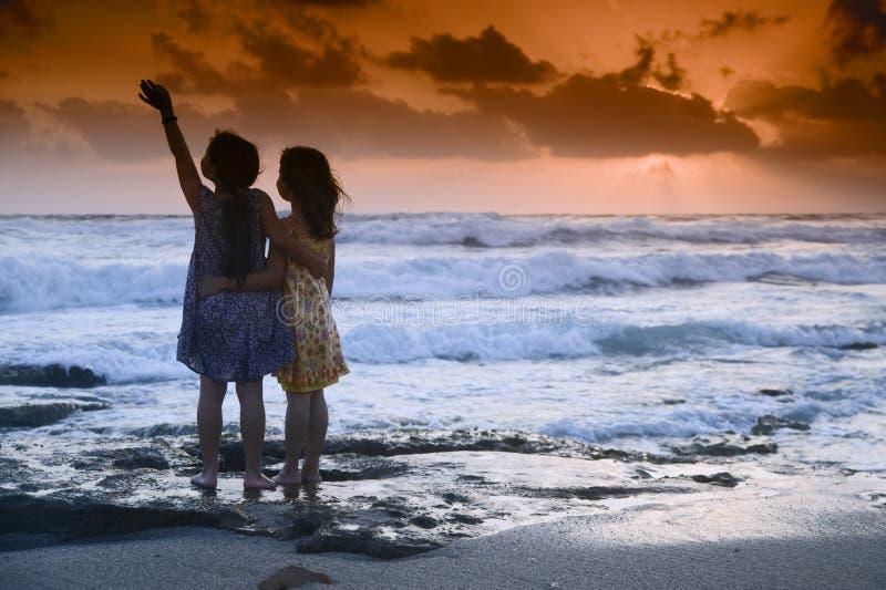 Puesta del sol de la playa de las muchachas imagen de archivo