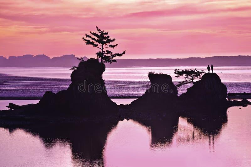Puesta del sol de la playa del océano con formaciones de roca y tonos rosados y púrpuras de la luz imagen de archivo