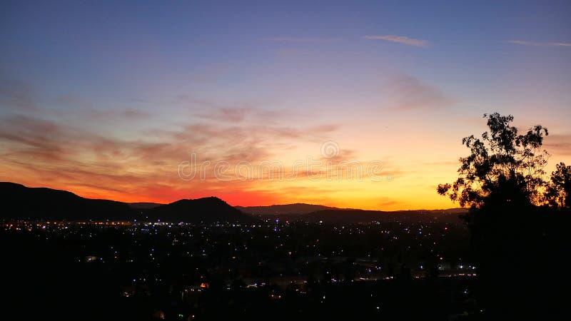 Puesta del sol de Los Ángeles sobre luces de la ciudad, amarillo y azul rojos imagen de archivo libre de regalías
