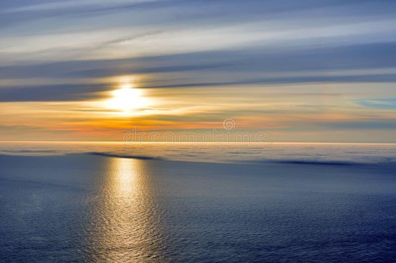 Puesta del sol del sol de medianoche sobre la mitad del océano cubierta en niebla del mar foto de archivo