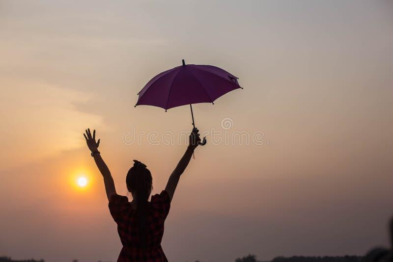 Puesta del sol de observación de la muchacha que sostiene un parasol de playa foto de archivo
