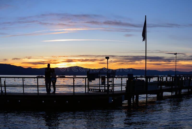 Puesta del sol de observación de los pares de la silueta en el lago foto de archivo