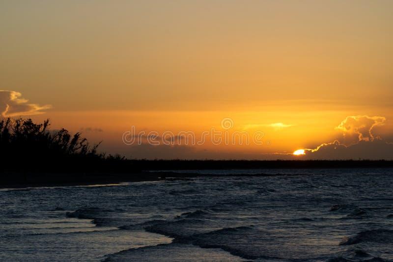 Puesta del sol de oro en el Caribbeans con las ondas minúsculas imagen de archivo