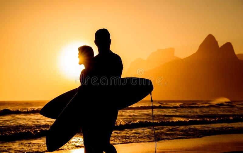 Puesta del sol de oro en la playa de Ipanema y dos siluetas de las personas que practica surf fotografía de archivo libre de regalías