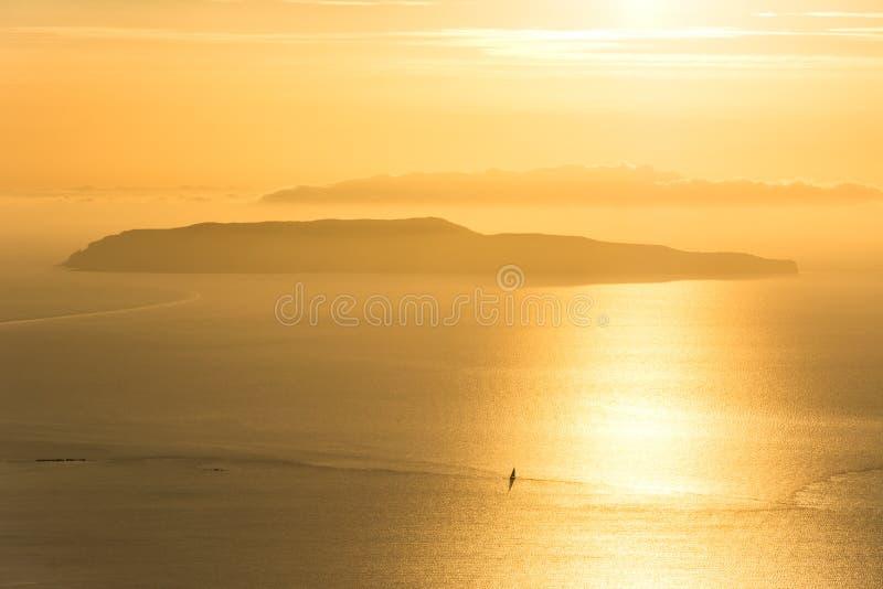 Puesta del sol de oro escénica sobre el océano con el barco de navegación solo y la isla en el fondo fotografía de archivo libre de regalías