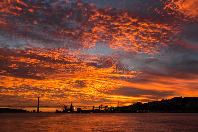 Puesta del sol de oro increíble sobre el río el Tajo, puente 25 de abril y el puerto de Lisboa, Portugal foto de archivo libre de regalías