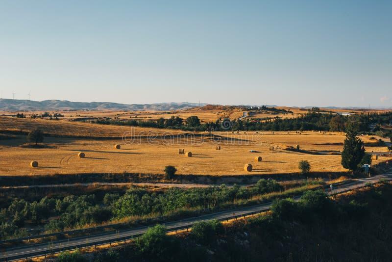 Puesta del sol de oro sobre campo de granja con las balas de heno imágenes de archivo libres de regalías