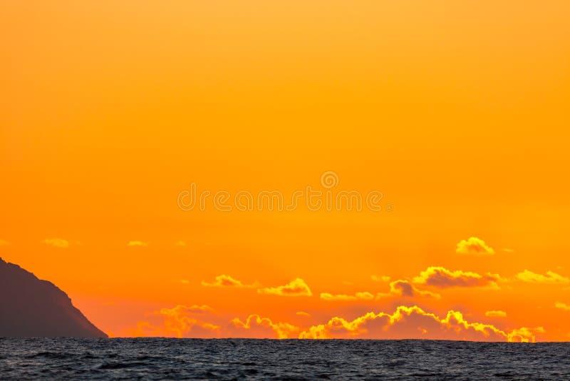 Puesta del sol de oro sobre el océano con las nubes dramáticas y el océano cambiante imagen de archivo