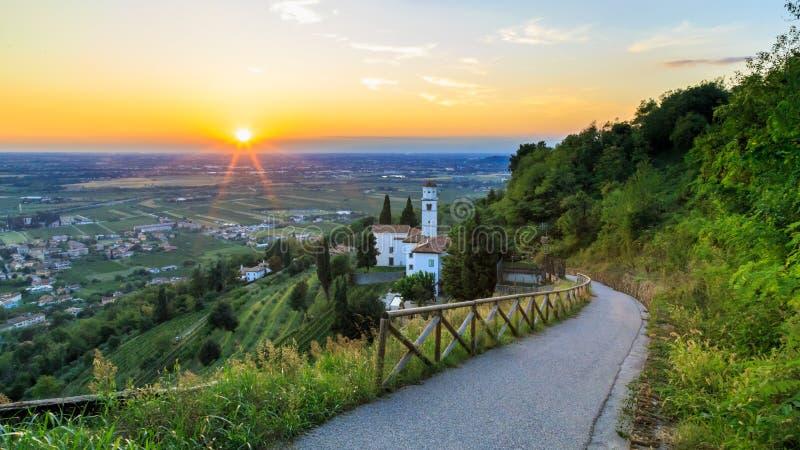 Puesta del sol de una colina con una iglesia abajo a los viñedos imágenes de archivo libres de regalías
